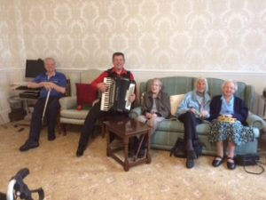 Geoff Stewart playing the accordian at Bushell House